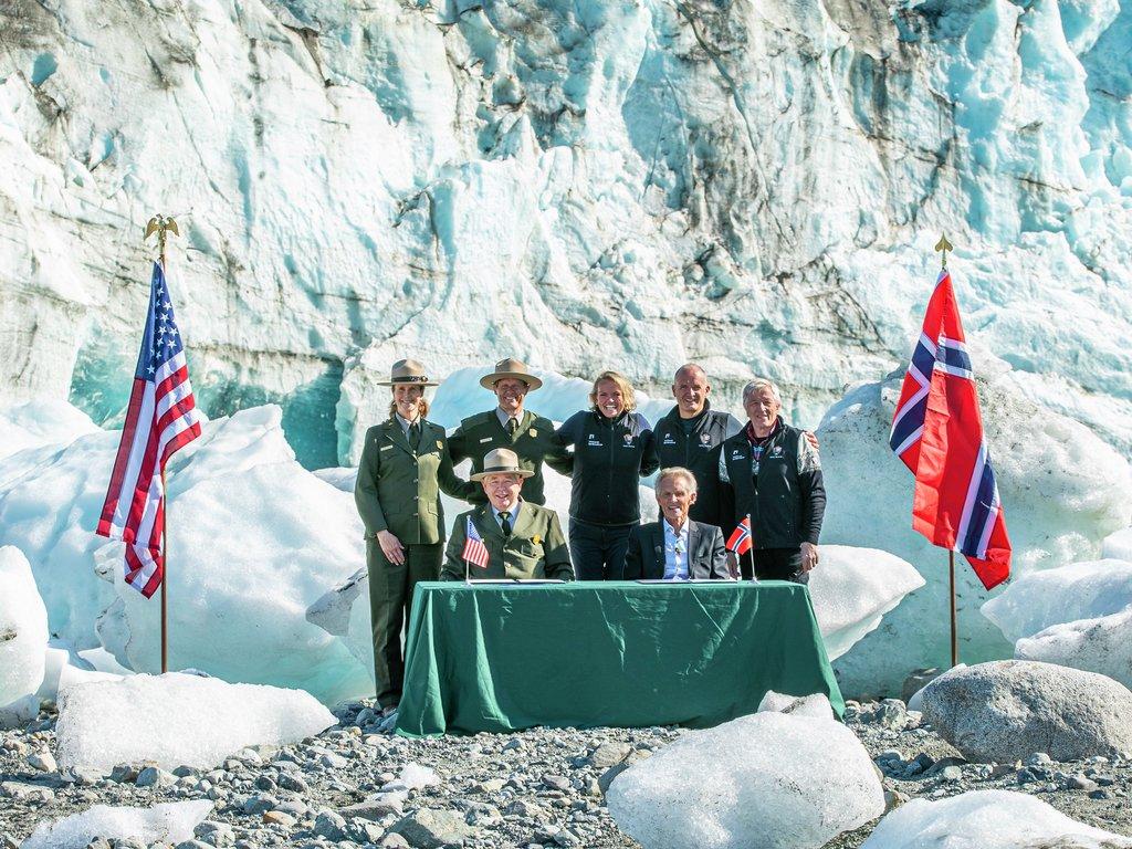 Foto frå signeringa av samarbeidsavtale mellom verdsarvområde i Noreg og Alaska. Representantane er samla framfor ein bre, med norsk og amerikansk flagg.