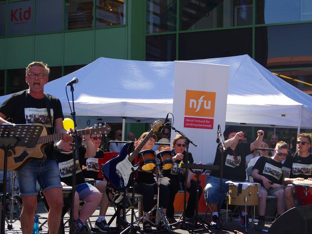 ASVO-bandet frå Årdal på Kulturfestivalen for utviklingshemma 2018. Åtte musikarar med ulike instrument på scenen på Elvetorget i Førde, publikum står rundt.