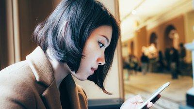 Kvinna söker information på mobilen
