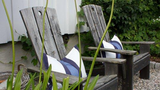 KRYDDER: Det hvite huset er omgitt av en stor grønn hage med grus- og helleganger. De blå innslagene er krydderet som løfter helheten. Foto: Bjørg Owren/ifi.no