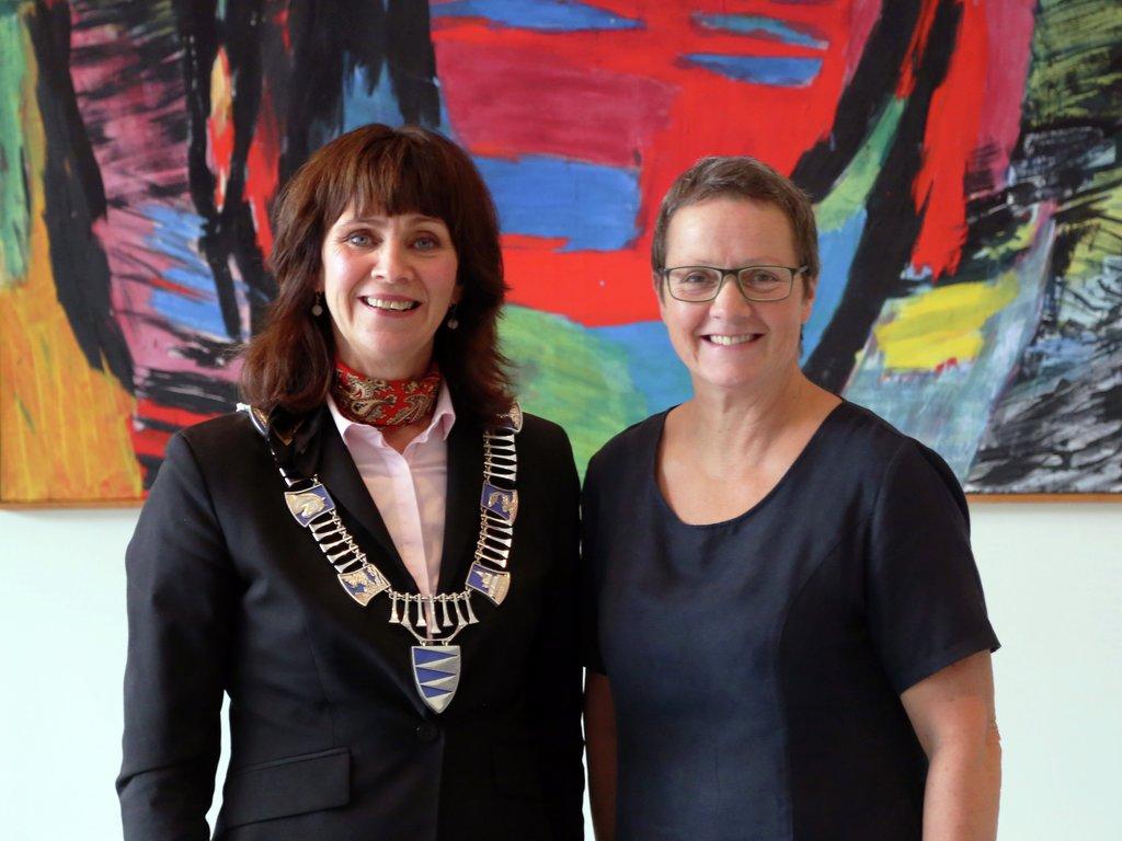 Fylkesordførar Jenny Følling og leiar for hovudutval for næring og kultur, Karen Marie Hjelmeseter, fotografert framfor eit abstrakt kunstverk på Kviknes Hotel i Balestrand.