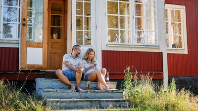 Mies ja nainen istuvat mökin portailla