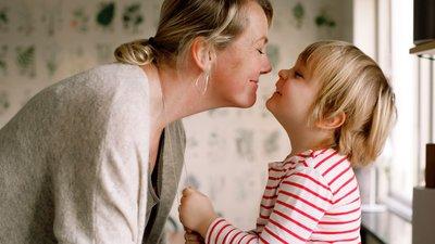 Äiti ja lapsi hymyilevät toisilleen lähekkäin