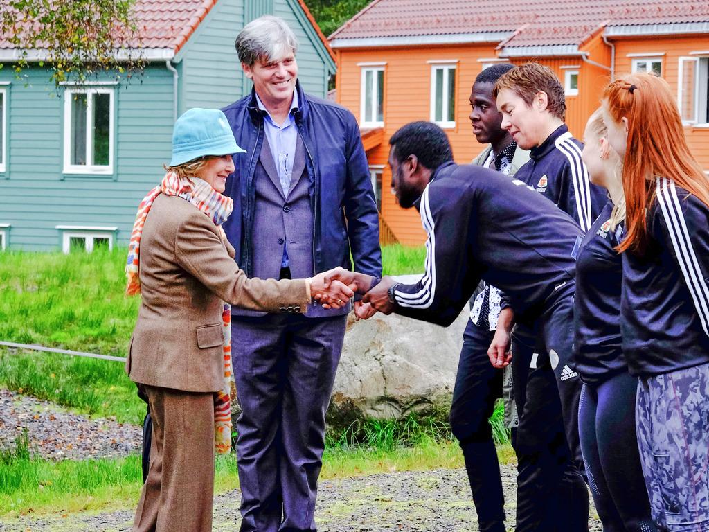 Foto av dronning Sonja som helser på elevar i elevbedrifta Trimigrering frå Flora.