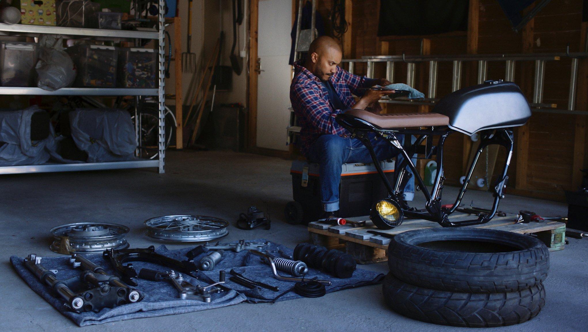 Mies kokoaa moottoripyörää tallissa
