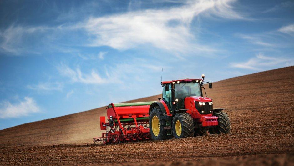 Rød traktor på jordet
