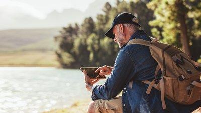 man med mobil vid vattnet