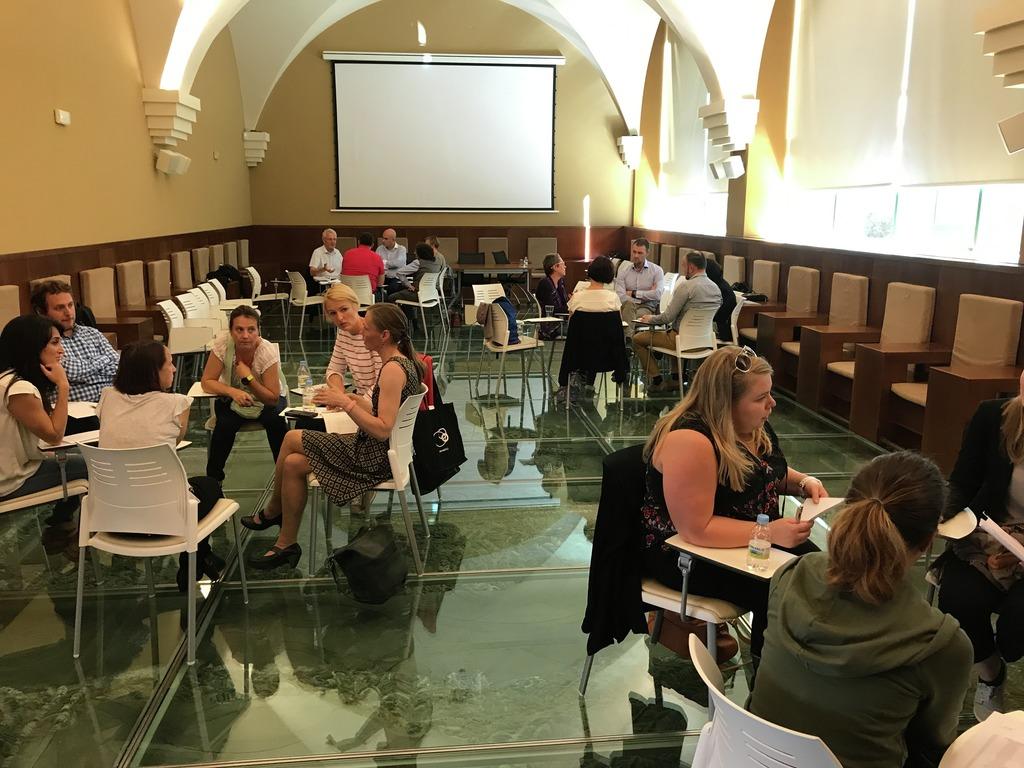 Foto av gruppearbeid frå eit stort rom/ein aula der fire grupper sit samla og diskuterer noko. Det er fem personar på kvar gruppe. Rommet er lyst og høgt under tak, golvet er grønt og i glas.