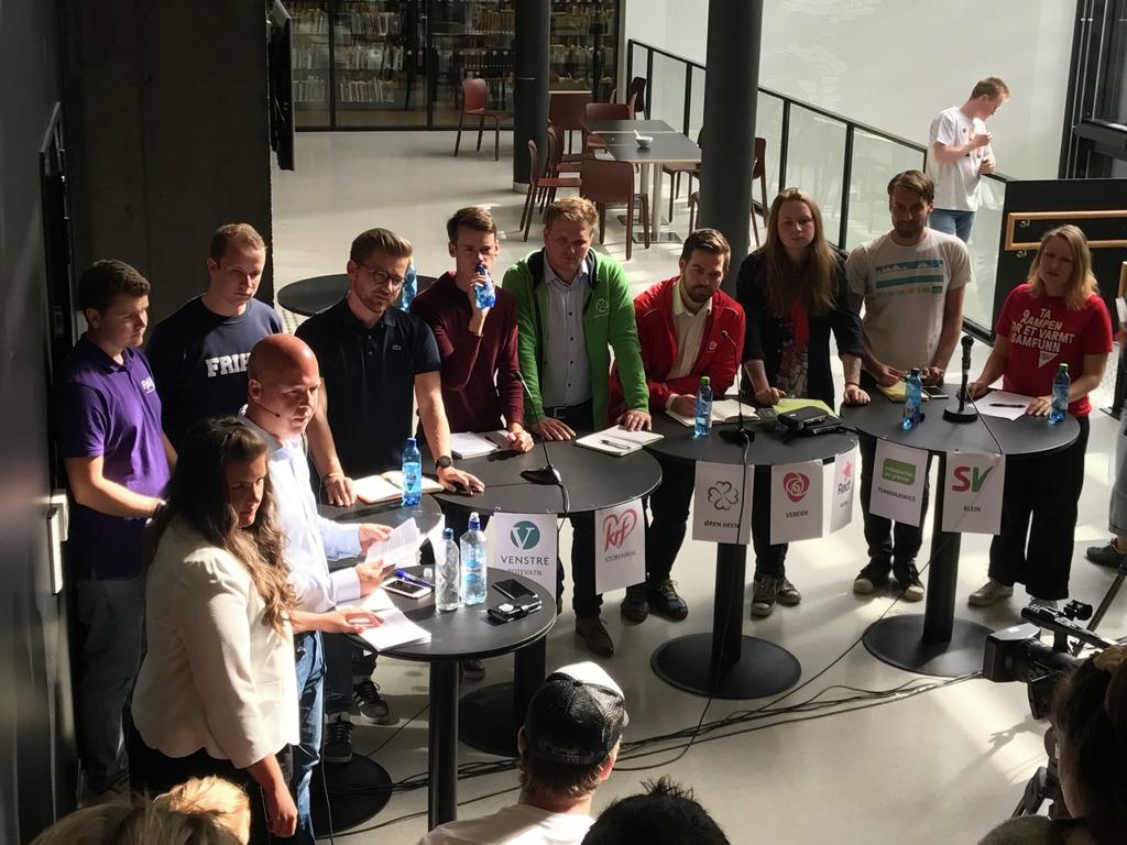 Foto frå politisk debatt mellom ungdomspartia på Høgskulen på Vestlandet. Ungdomspolitikarane er samla ståande rundt små, runde bord.