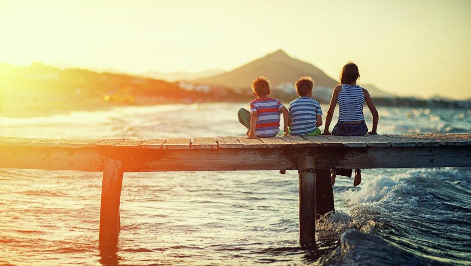 Familj på brygga i solnedgång