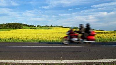 Moottoripyörä ajaa maalaismaisemassa