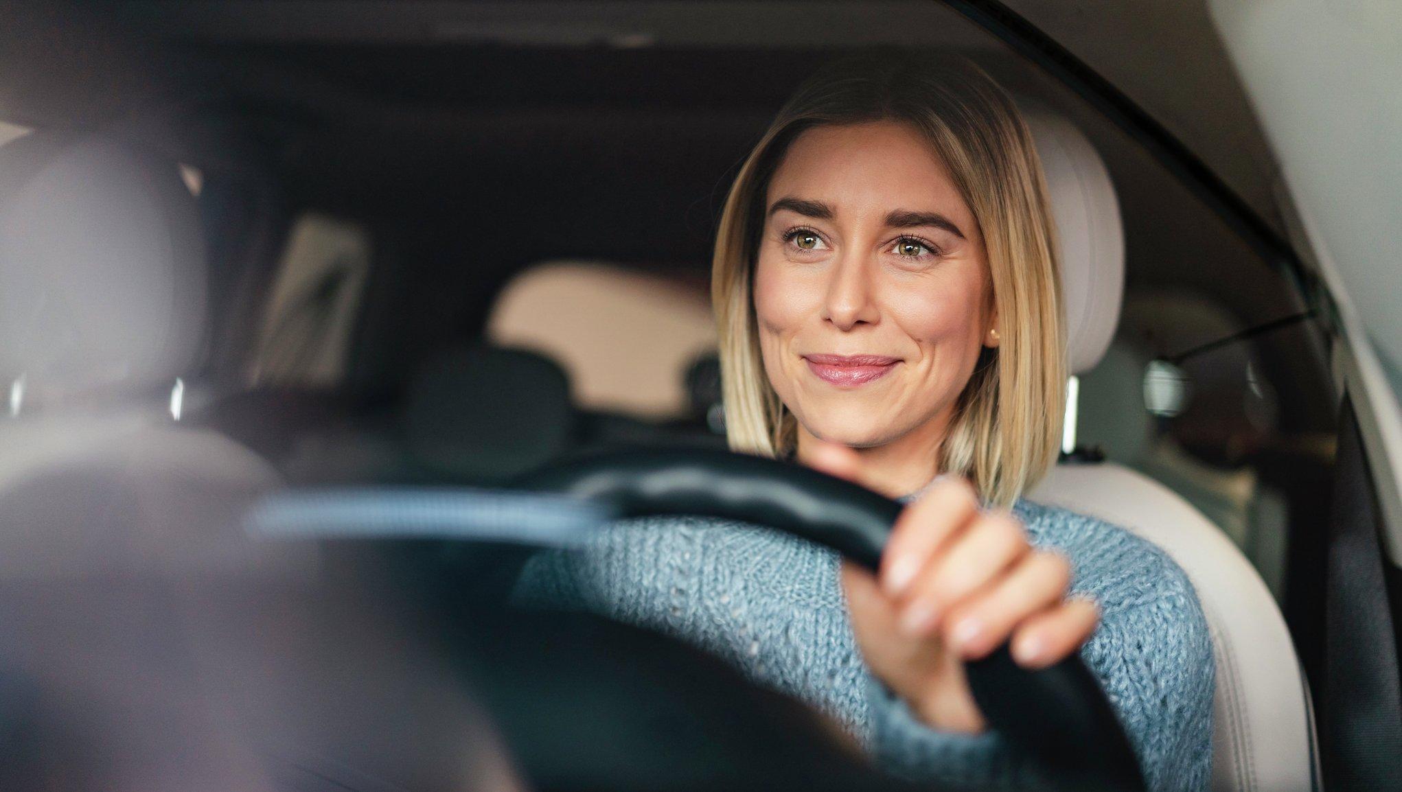 Kvinde smiler sidende bag rettet i sin bil
