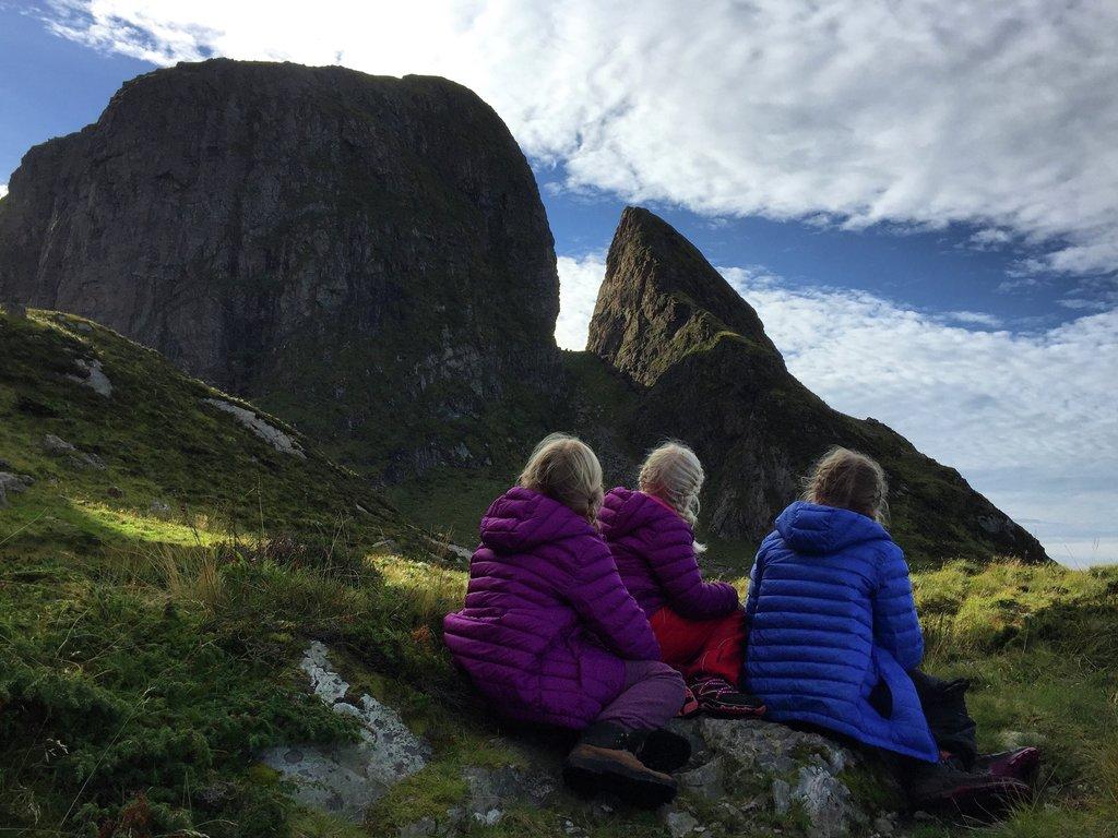Foto av tre ungar i dunjakker som sit og ser mot fjellet Kinnaklova på Kinn.