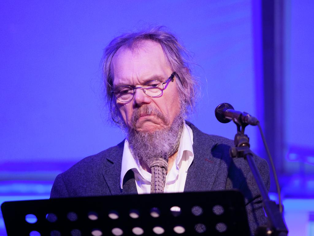Foto av Fridtjov Urdal som kåserer. Han står ved ein mikrofon og eit notestativ som held notata sine. Han er kledd i dress og skjerf, og det er blått lys i rommet.