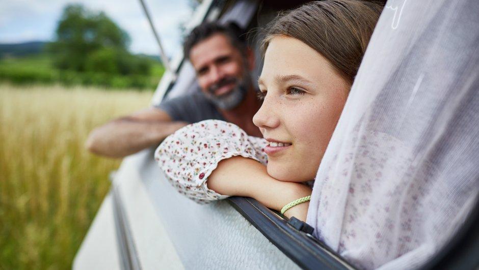 Tyttö ja mies katsovat ulos matkailuvaunun ikkunasta