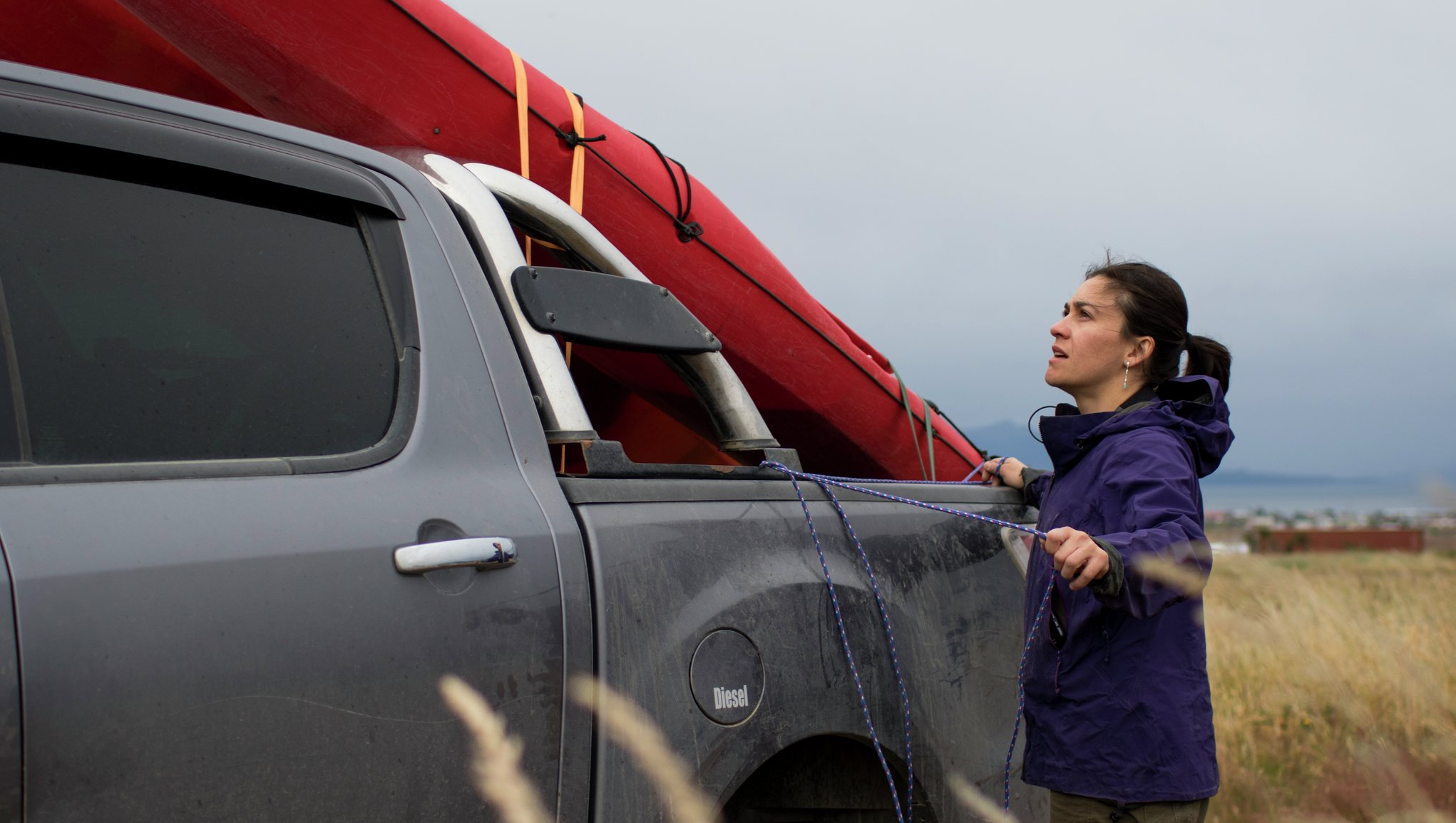 En kvinna fäster surfbräda på biltak
