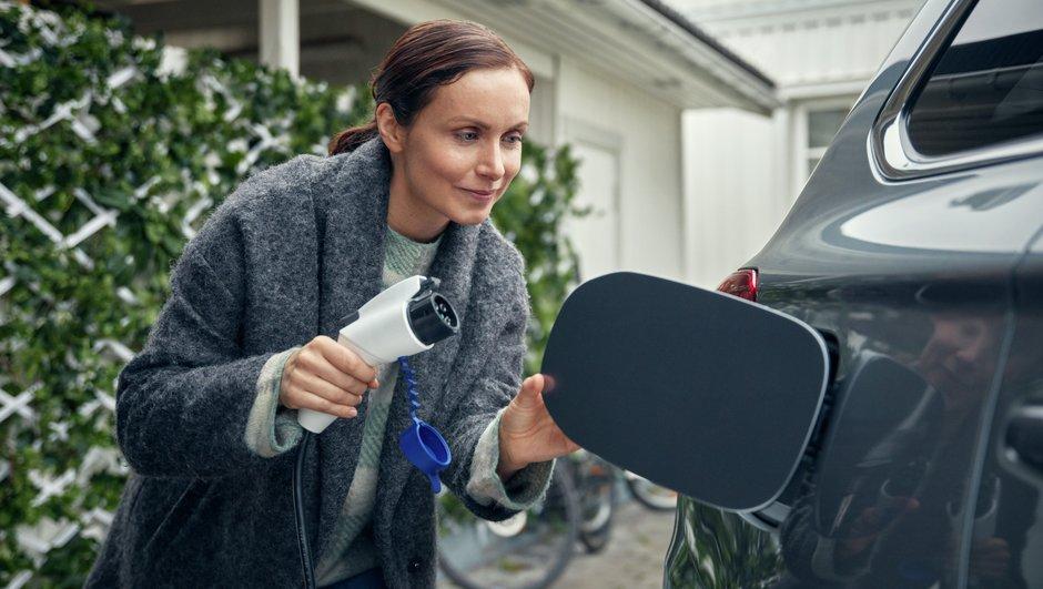 Nainen lataamassa sähköautoa