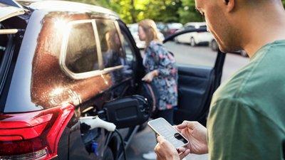 Mies katsoo älypuhelinta sähköautoa ladattaessa