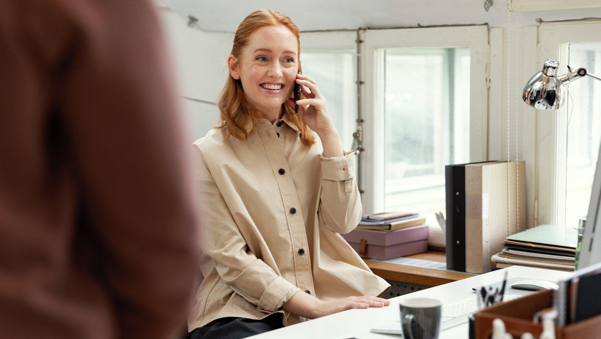 Nainen puhuu puhelimeen toimistolla