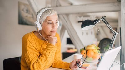 woman working with pc wearing headset.