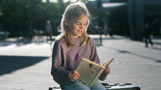 Sommerles: jente som leser bok på koffert