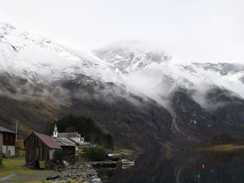 Foto frå Bakka i Nærøyfjorden. Biletet er teke nede ved fjorden, og vi ser eit par naust og kyrkja i bakgrunnen. Skodda heng nedover fjellsidene, og fjelltoppane har fått eit snødryss.