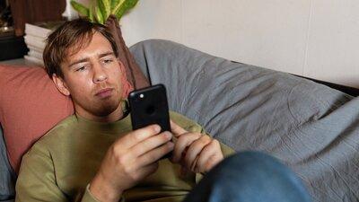 Ung mand ligger og kigger på sin mobil i sofaen