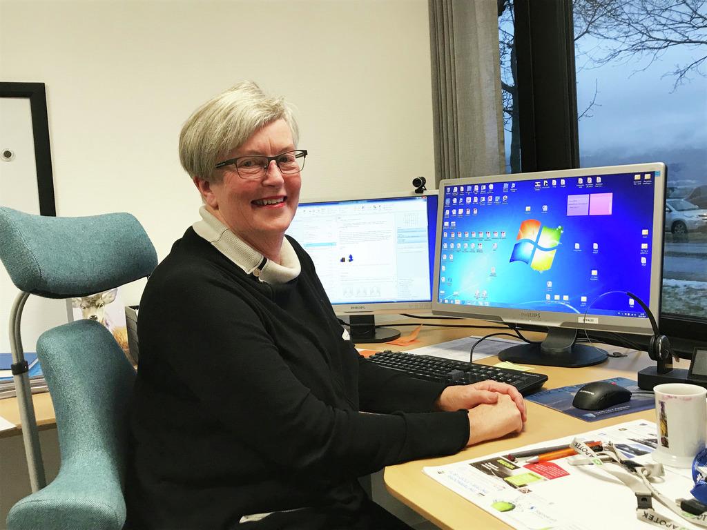 Foto av rådgjevar og folkehelsekoordinator i den offentlege tannhelsetenesta, Britt Sønnesyn. Ho sit ved pc-en på kontoret sitt.
