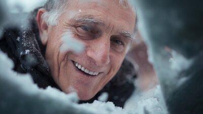 man tittar in genom snöig bilruta