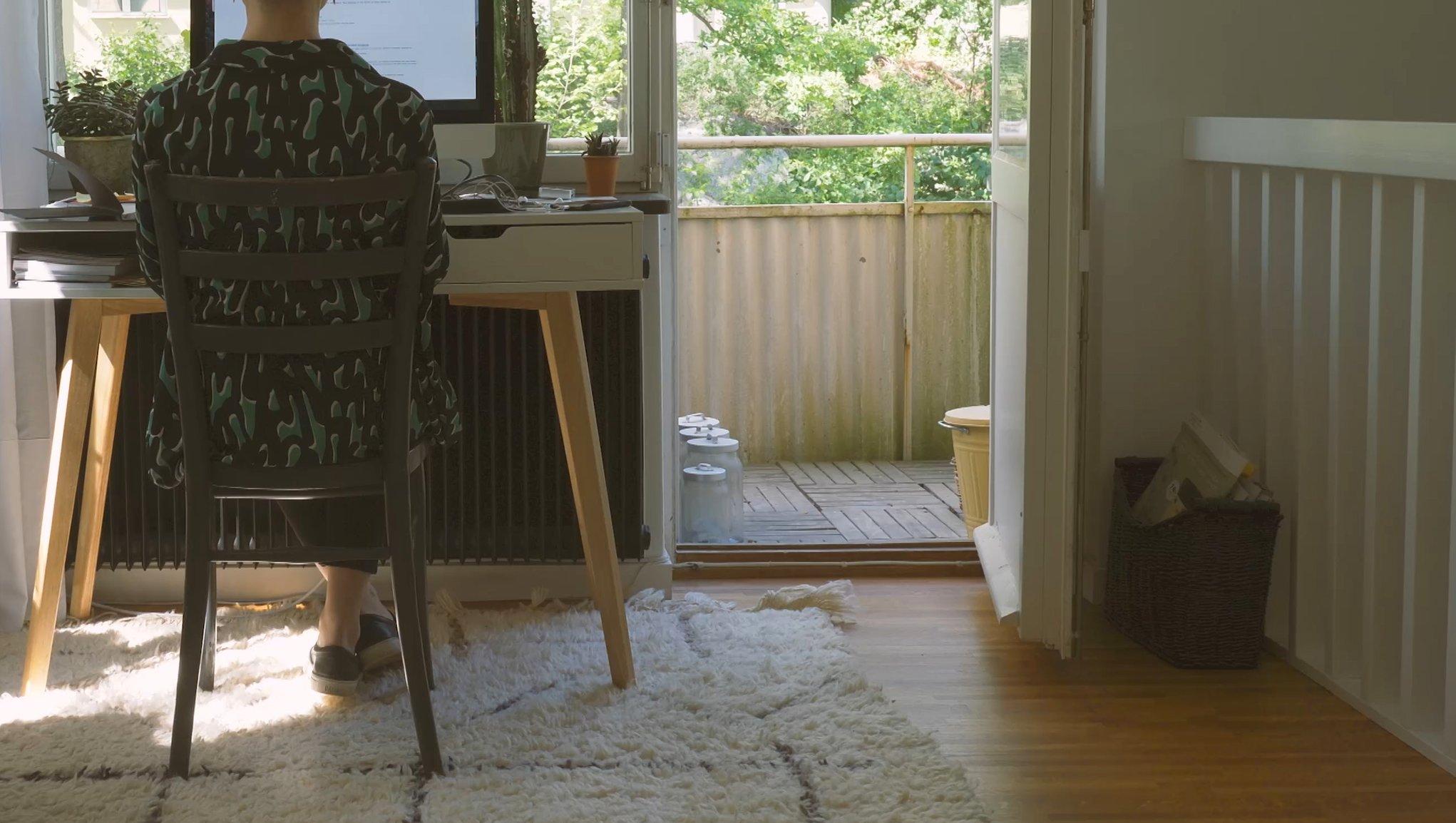 En kvinna sitter vid datorn vid en balkong