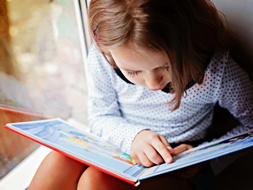 Foto av ung jente som les i ei bok.