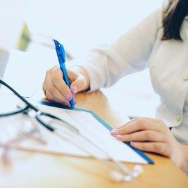 kvinna skriver på papper