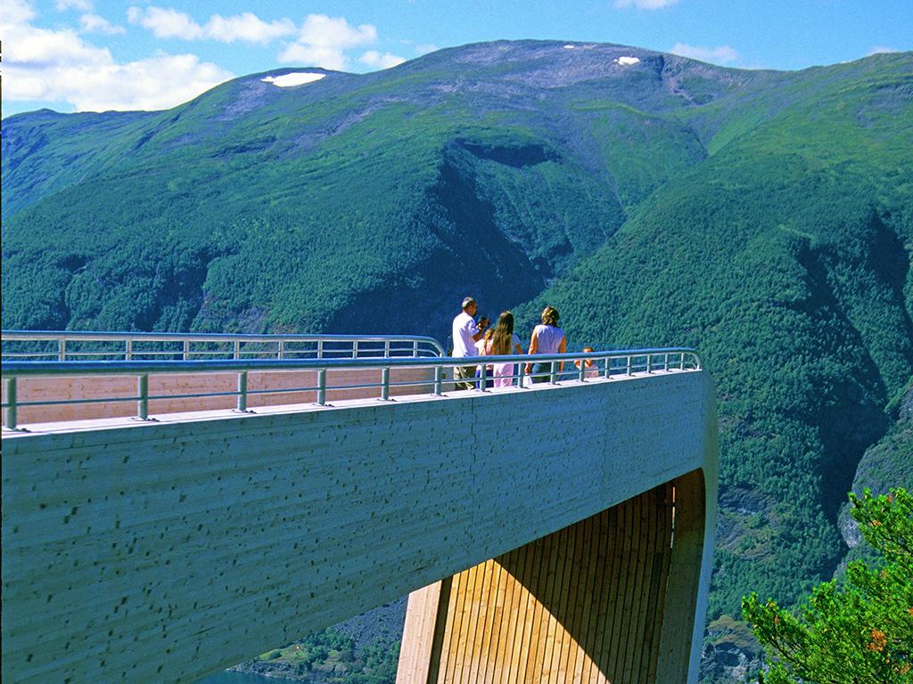 Foto frå utsiktspunktet på Stegastein i Aurland. Vi ser nokre folk stå ute på utsiktspunktet, det er blå himmel, sol og grøne tre.