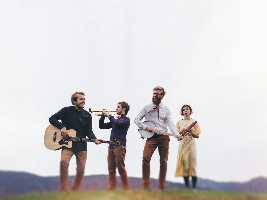 Foto av musikkgruppa Bart Clavier. Dei poserer ute med fjell og kvit himmel i bakgrunnen. Det er tre menn og ei kvinne som held og spelar på ulike instument.