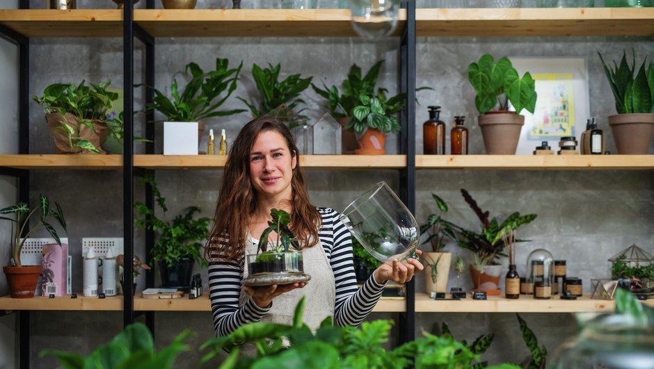 Kvinne i blomsterbutikk som viser frem en plante
