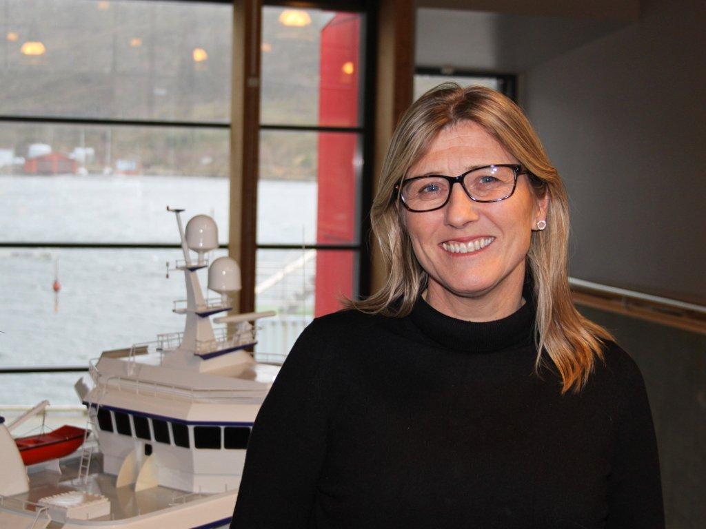 Portrettfoto av Mona Bakke Svarstad, ho står ved ein båtmodell med utsikt mot sjøen og smiler.