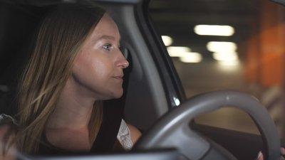 Nainen katsoo autosta ulos pimenevässä kesäillassa