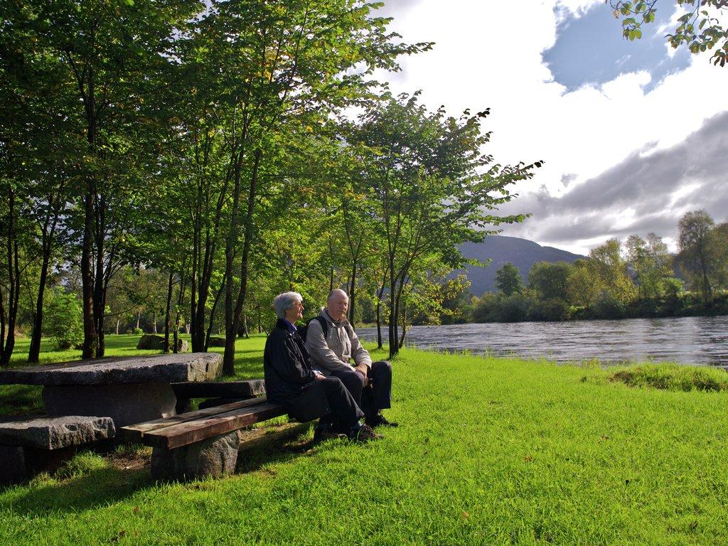 Foto av ein eldre mann og ei eldre dame, som sit på ein benk i parken ved elva i Førde. Det er grønt gras og sol.