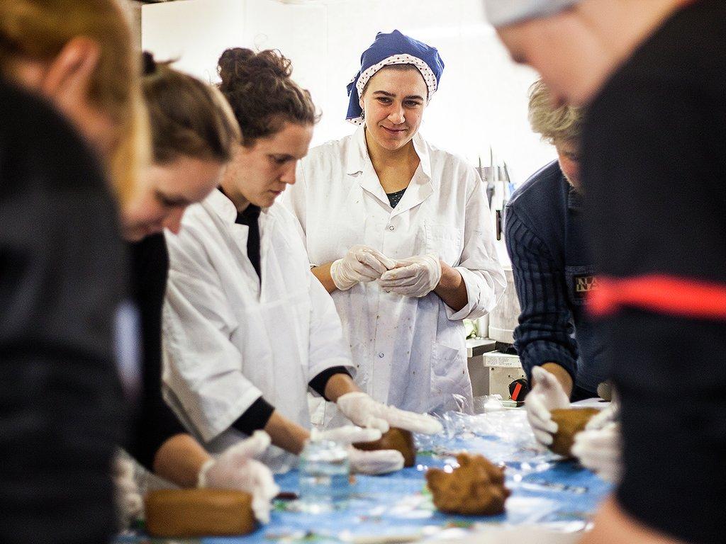Undervisning i ysting ved Sogn Jord- og hagbruksskule, elevar står rundt eit bord og klappar brunost medan ein lærar ser på.