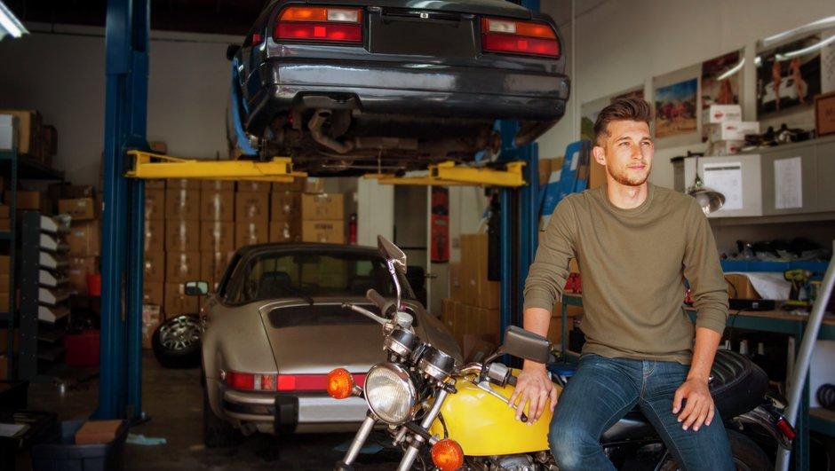 Mies autotallissa moottoripyötän ja käytettyjen autojen kanssa.