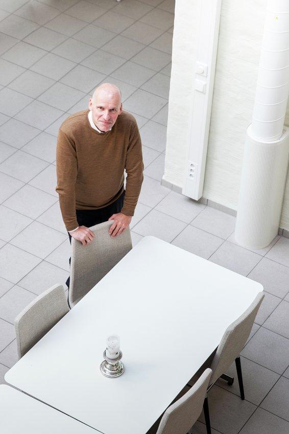 Geir Lippestad lener seg til en stol ved et hvitt bord, fotografert ovenfra