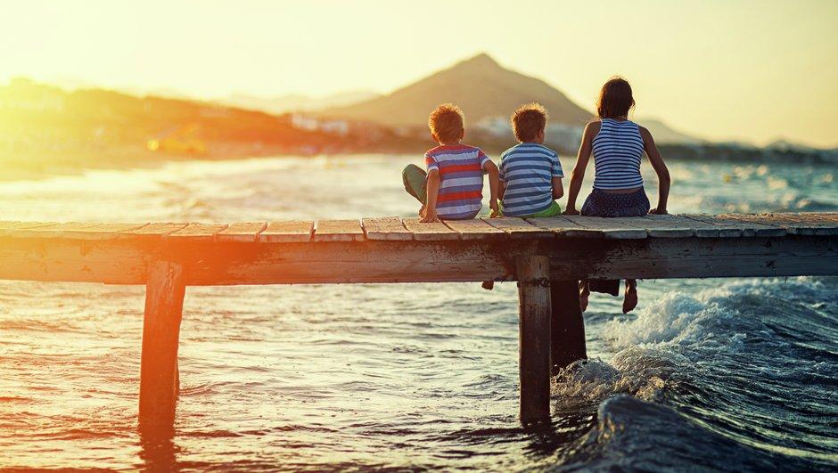 Barnfamilj på bryggan i solnedgång