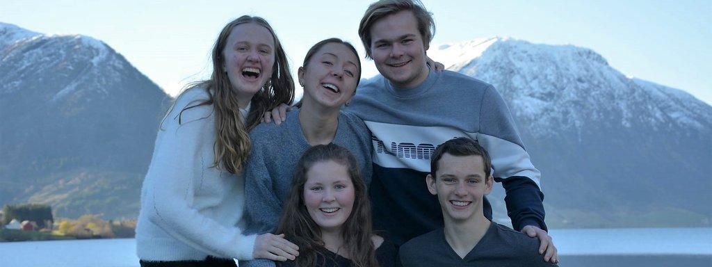 Foto av medlemmane i ungdomspolitisk utval 2018/2019 ved Jølstravatnet ein seinhaustdag i sol.