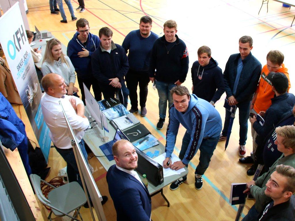 Foto frå marin karrieredag i Nordfjordhallen i september 2019. Ein gjeng elevar står samla rundt standen til opplæringskontoret for fiskeri og havbruk.