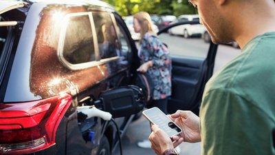 En man ser på sin smartmobil medan elbilen laddas