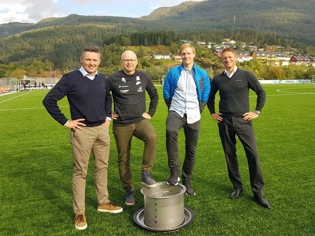 Fire menn som står på ein grøn kunstgrasbane i solskinn. Fjell og hus i bakgrunnen. Dei fire er Trond Teigene, Svein Olav Myklebust, Frank Tore Tveit, Tore Dvergsdal.
