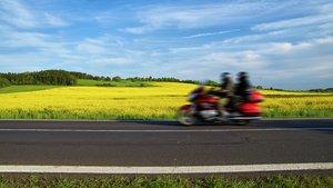 Kaksi henkilöä ajaa nopeasti ohi moottoripyörällä peltomaisemassa