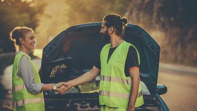 Nainen ja mies kättelevät tien sivuun vedetyn auton äärellä.