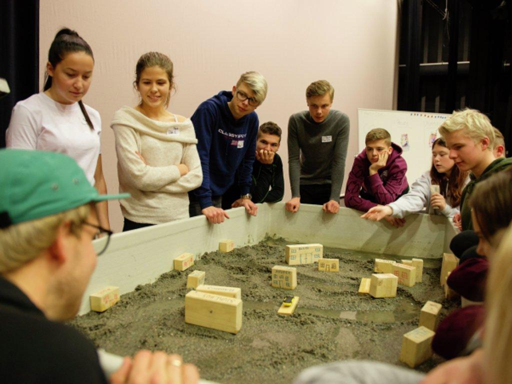 Ei gruppe elevar står rundt ein kasse med sand og klossar som skal illustrere flaum.