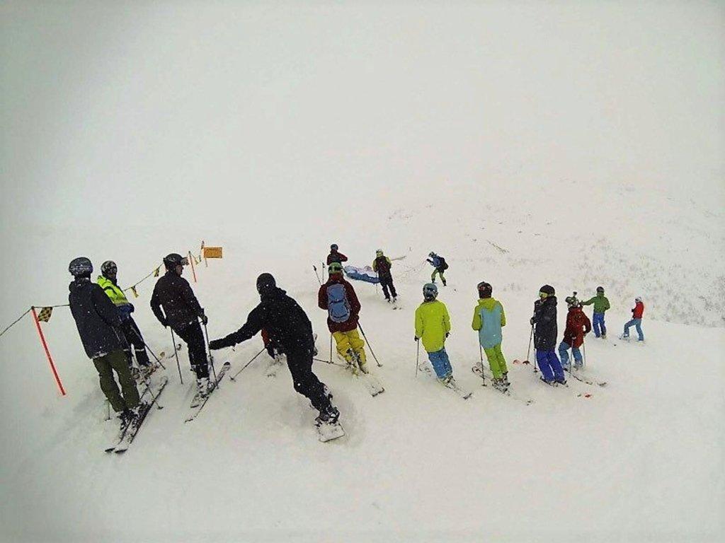 Foto av ungdom i tildels fargerike kle på toppen av ein skibakke. Vi ser dei bakfrå.